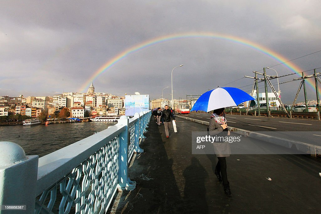 A rainbow is seen over the Galata bridge and Galata Tower as a woman walks with her umbrella after a rainy day in Istanbul on November 23, 2012.