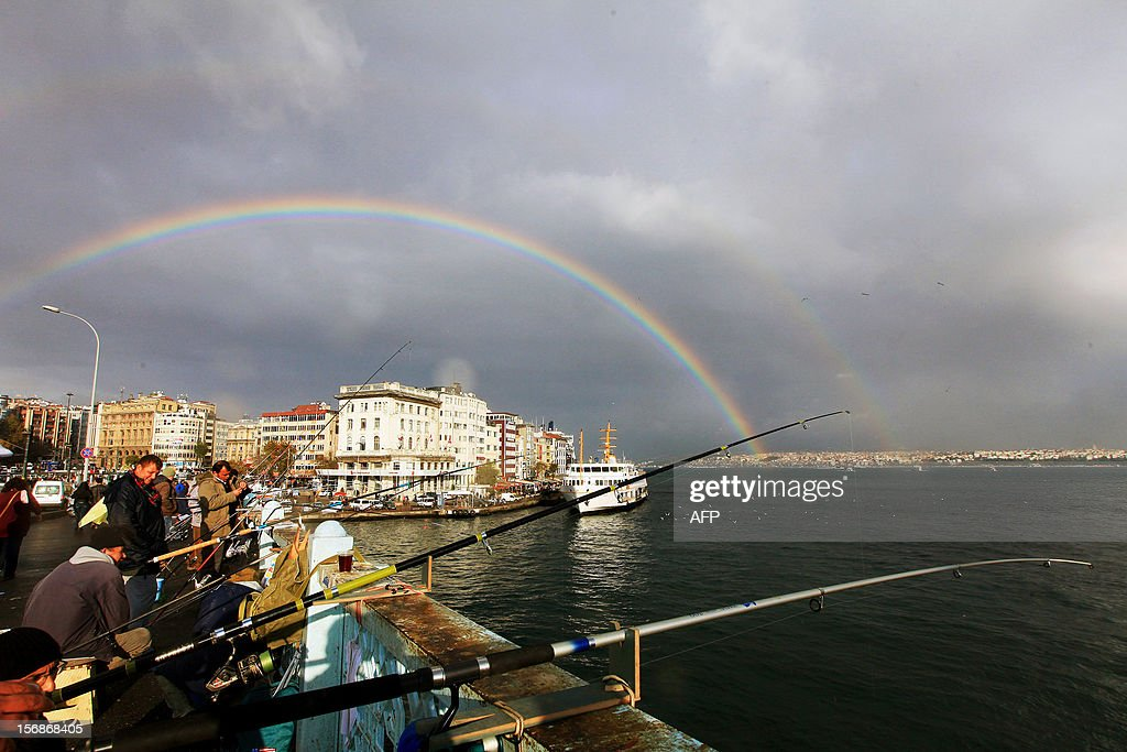 A rainbow is seen over the Galata bridge and Galata Tower while people are fishing after a rainy day in Istanbul on November 23, 2012. AFP PHOTO/MIRA
