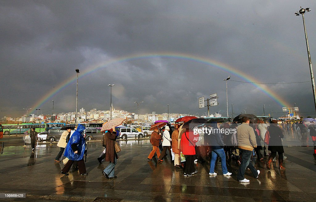 A rainbow is seen over the Galata bridge and Galata Tower while people are walking with their umbrellas after a rainy day in Istanbul on November 23, 2012.