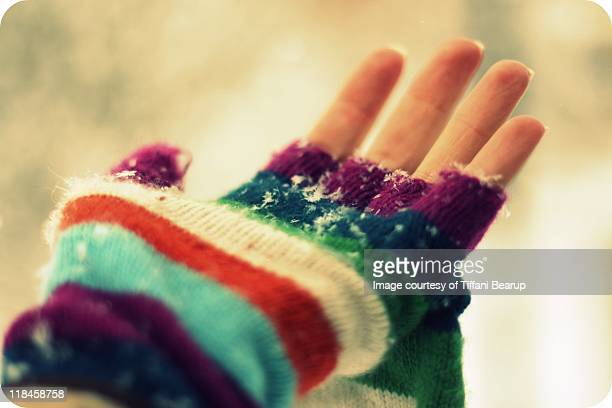 Rainbow knitted glove catching snowflakes