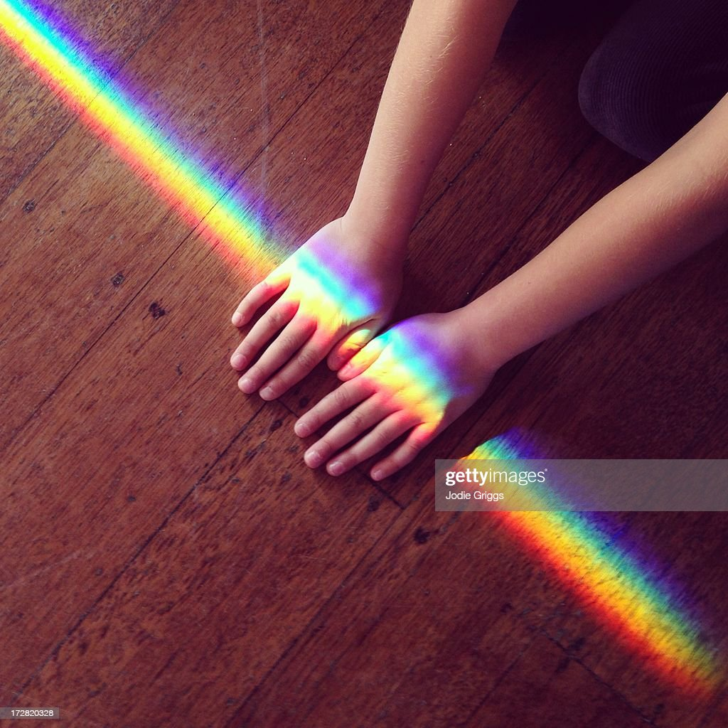 Rainbow light crossing hands of a child on ground : Stock Photo