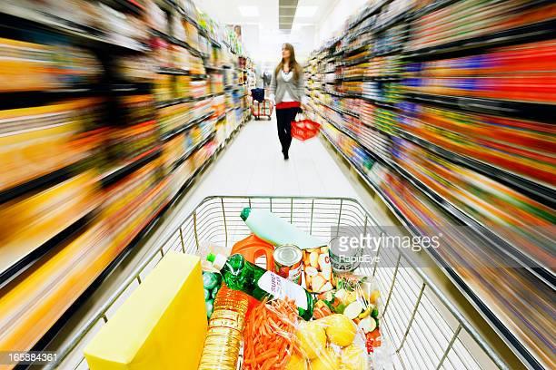 Rainbow motion blur as shopping cart speeds through supermarket