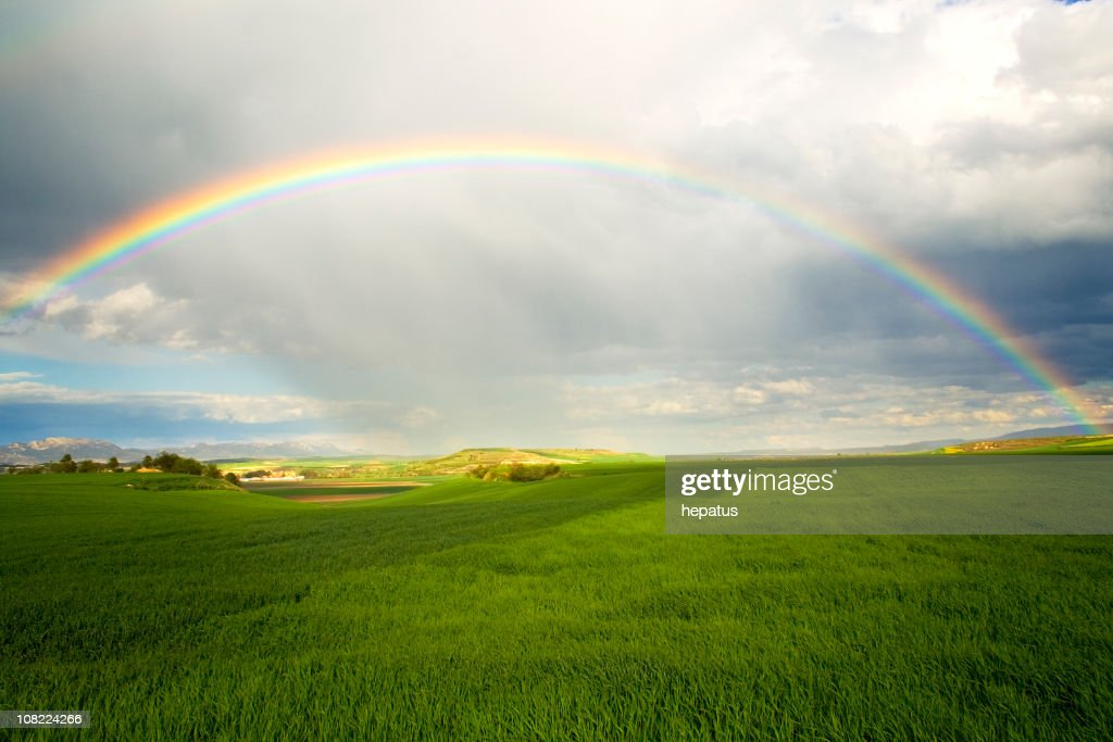 A rainbow over a green field with rain clouds : Stock Photo
