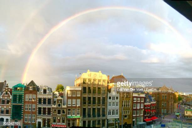 Rainbow Over Buildings Against Cloudy Sky