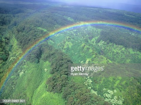 Rainbow over green hills, aerial view : Stock Photo