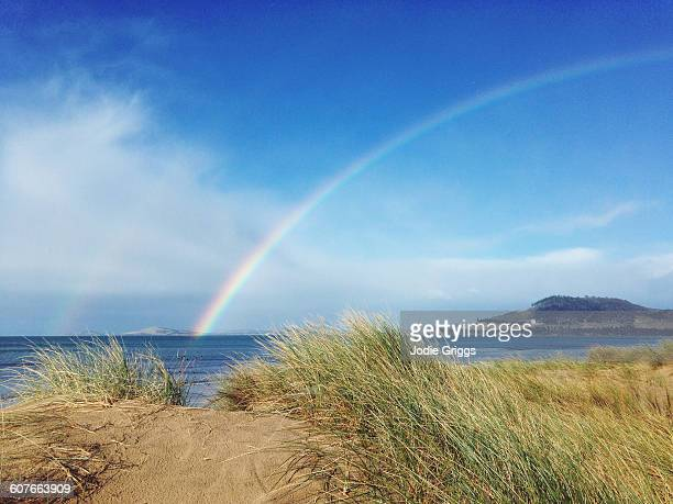 Rainbow over the sand dunes and ocean
