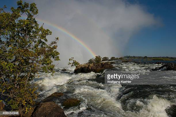 Rainbow over Victoria Falls seen from the shore of the Zambezi River at the section above the falls near Livingston in Zambia