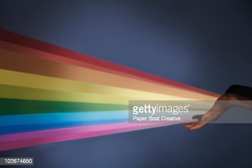 Rainbow projection coming out of woman's hand : Photo