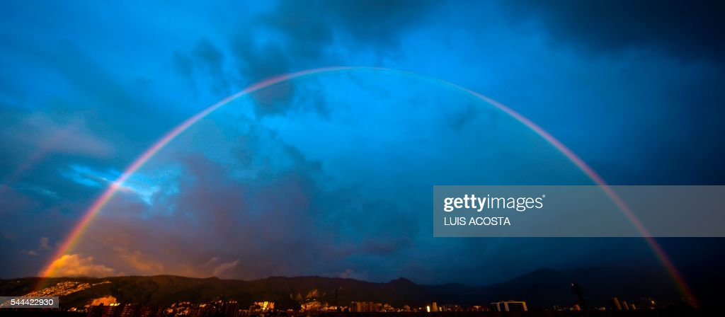 A rainbow seen during sunset in Bogota on June 3, 2016. / AFP PHOTO / Luis Acosta