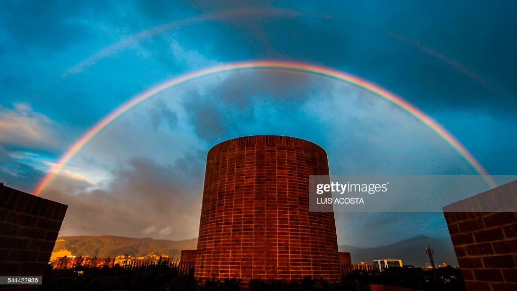 TOPSHOT - A rainbow seen during sunset in Bogota on June 3, 2016. / AFP PHOTO / Luis Acosta