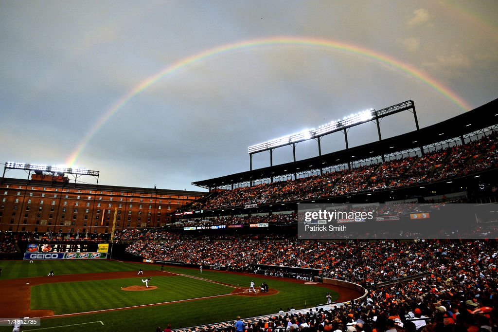 A rainbow shines in the sky as pitcher Kevin Gausman #37 of the Baltimore Orioles works batter Alberto Gonzalez #40 of the New York Yankees in the fourth inning at Oriole Park at Camden Yards on June 28, 2013 in Baltimore, Maryland.