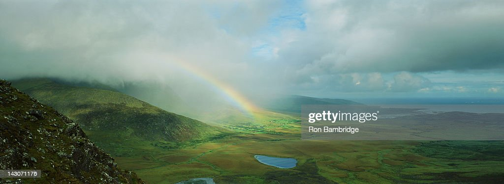 Rainbow stretching over rural landscape : Stock Photo