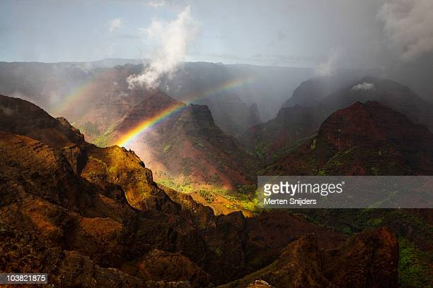 Rainbow stretching over Waimea Canyon.