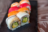 Closeup view of colorful Japanese sushi rolls served on black tray in restaurant