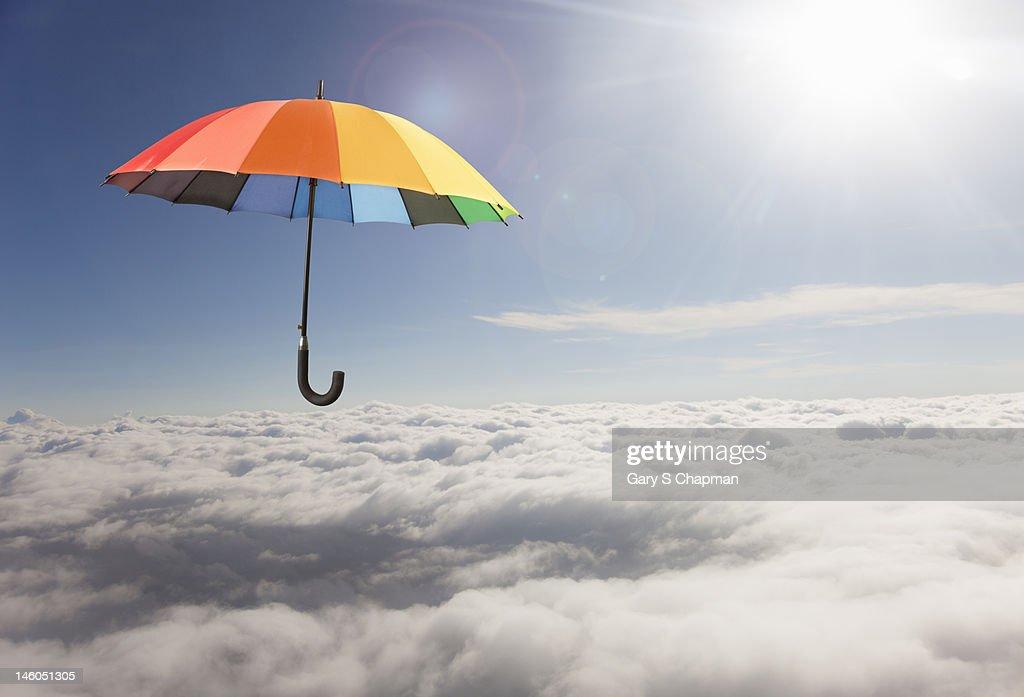 Rainbow umbrella floating above clouds : Stock Photo