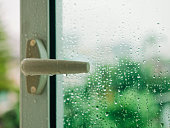 Raindrop on window with Handle Blur tree background Rainy Season