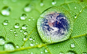 planet earth inside a raindrop closeup on a green leaf ,