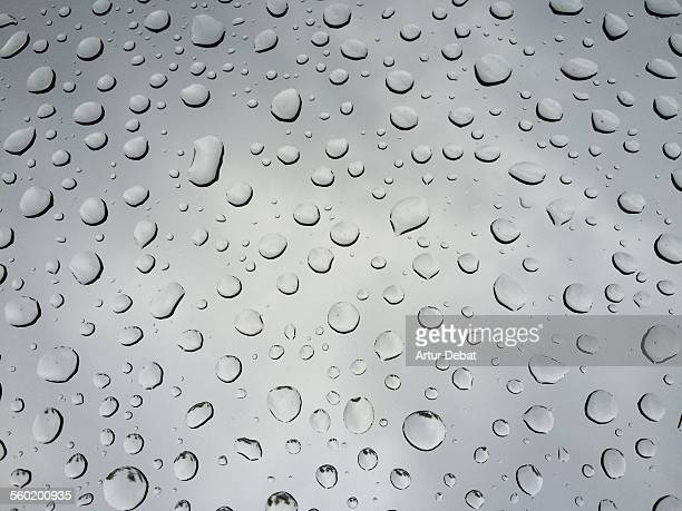 Raindrops on glass window with cloudy sky