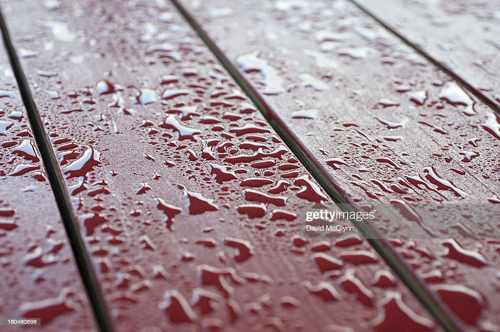 Raindrops on the surface of a picnic table : Stock Photo