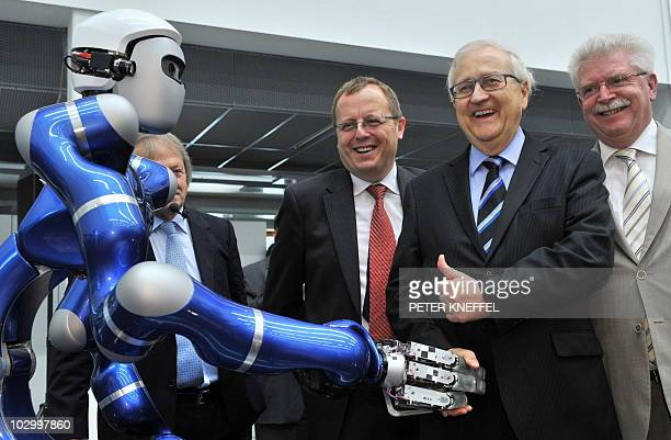 Rainer Bruederle German Minister of Economics and Technology shakes hands with robot 'Justin' as Bavaria's Economy Minister Martin Zeil and the...