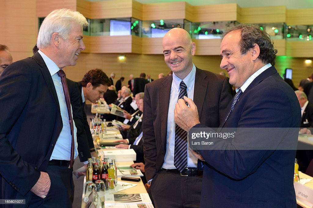 Rainer Holzschuh, publisher of the Kicker Sportmagazin, talks to UEFA president Michel Platini and UEFA general secretary Giovanni Infantino during the DFB Bundestag at NCC Nuremberg on October 25, 2013 in Nuremberg, Germany.