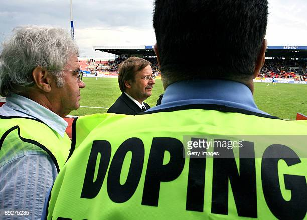 Rainer Koch Vice President of the German Football Association and two antidoping inspectors socalled chaperones stand next to the pitch during the 3...