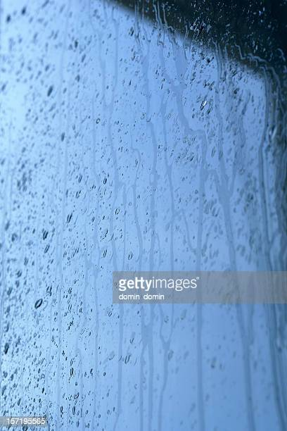 Raining cats and dogs, water drops flowing down the glass