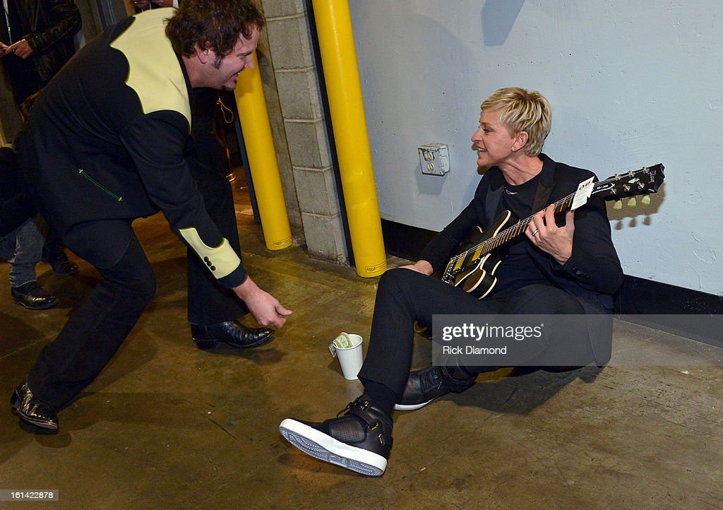 Rainn Wilson offers <a gi-track='captionPersonalityLinkClicked' href=/galleries/search?phrase=Ellen+DeGeneres&family=editorial&specificpeople=171367 ng-click='$event.stopPropagation()'>Ellen DeGeneres</a> some change backstage at the 55th Annual GRAMMY Awards at STAPLES Center on February 10, 2013 in Los Angeles, California.