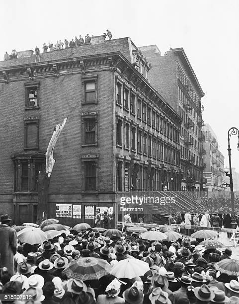 Rainspattered crowds jam the streets outside the fourstory brownstone home of the hermit Collyer brothers as police begin their search of the...