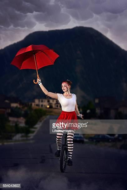 Regnerischen Nacht Acrobat mit roten Regenschirm