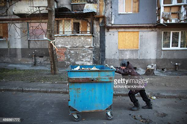 Raisa Zinkovskaya pushes a dumpster next to damaged apartments following last September shelling in the in Kievskiy district of the Eastern Ukraine...