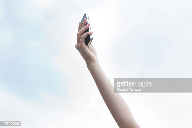 Raised arm with smartphone with sky background