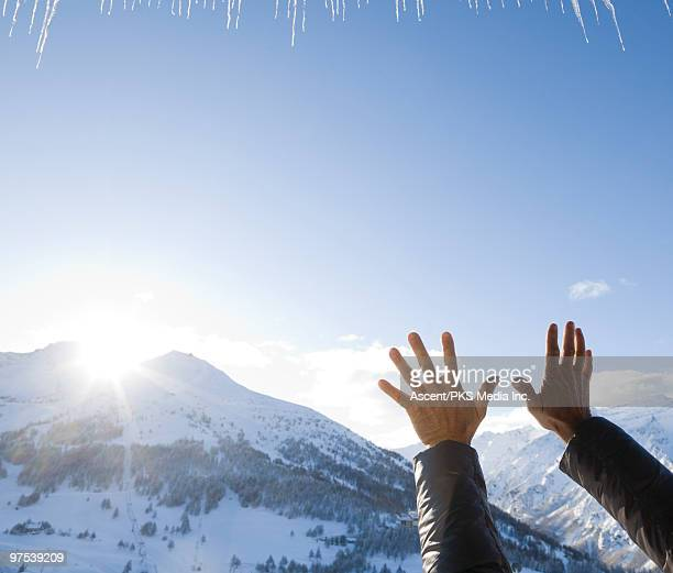 Raised hands embrace sunrise over snowy mountains