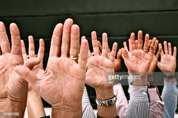 Raised hands of male and female participants of the meeting