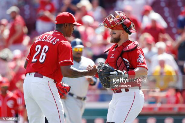 Raisel Iglesias and Tucker Barnhart of the Cincinnati Reds celebrate after the final out in the ninth inning against the San Diego Padres at Great...