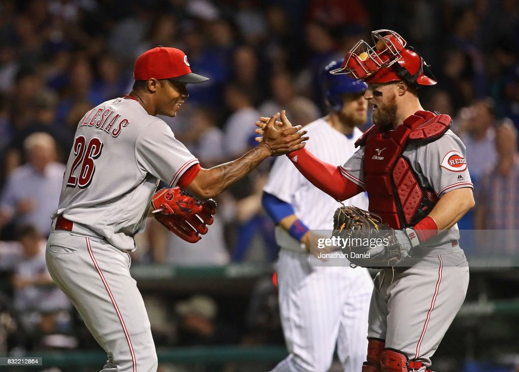 Raisel Iglesias #26 of the Cincinnati Reds (L) celebrates with Tucker Barnhart #16 after a win against the Chicago Cubs at Wrigley Field on August 15, 2017 in Chicago, Illinois. The Reds defeated the Cubs 2-1.