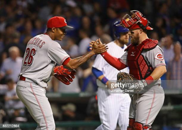 Raisel Iglesias of the Cincinnati Reds celebrates with Tucker Barnhart after a win against the Chicago Cubs at Wrigley Field on August 15 2017 in...