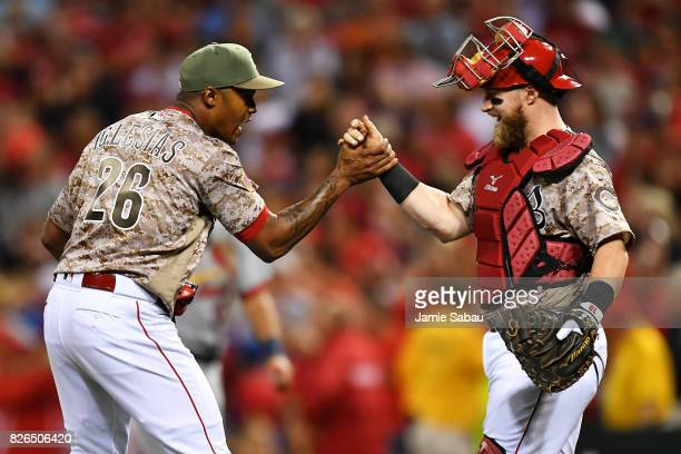 Raisel Iglesias of the Cincinnati Reds celebrates with Tucker Barnhart of the Cincinnati Reds after the final strike out in the ninth inning against...