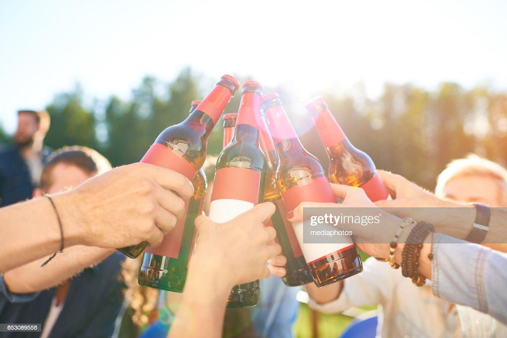 乾杯のビール瓶を上げる : ストックフォト
