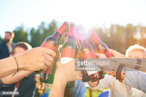 Raising beer bottles to toast : Stock Photo
