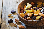 Assortment of raisins and various nuts in a wooden bowl on old table. Close-up. Bio healthy food. Selective focus