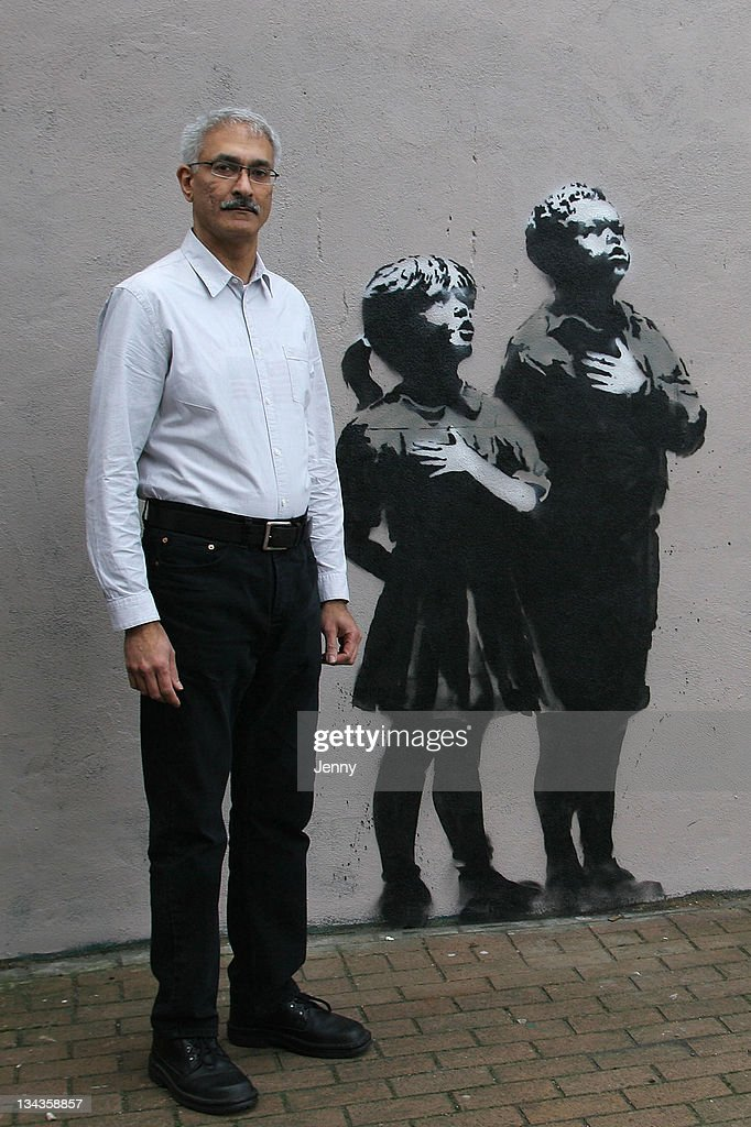 Raj Chavda, proprietor of a chemist's, stands beside the outside wall of the premises on which some artwork attributed to <a gi-track='captionPersonalityLinkClicked' href=/galleries/search?phrase=Banksy&family=editorial&specificpeople=157604 ng-click='$event.stopPropagation()'>Banksy</a>, the famed graffiti artist, has recently appeared on March 04, 2008 in north London, England. The scene depicts children gathering around a flagpole on which a plastic Tesco supermarket bag is flying. The artwork appeared on the wall on Sunday, March 2, 2008.