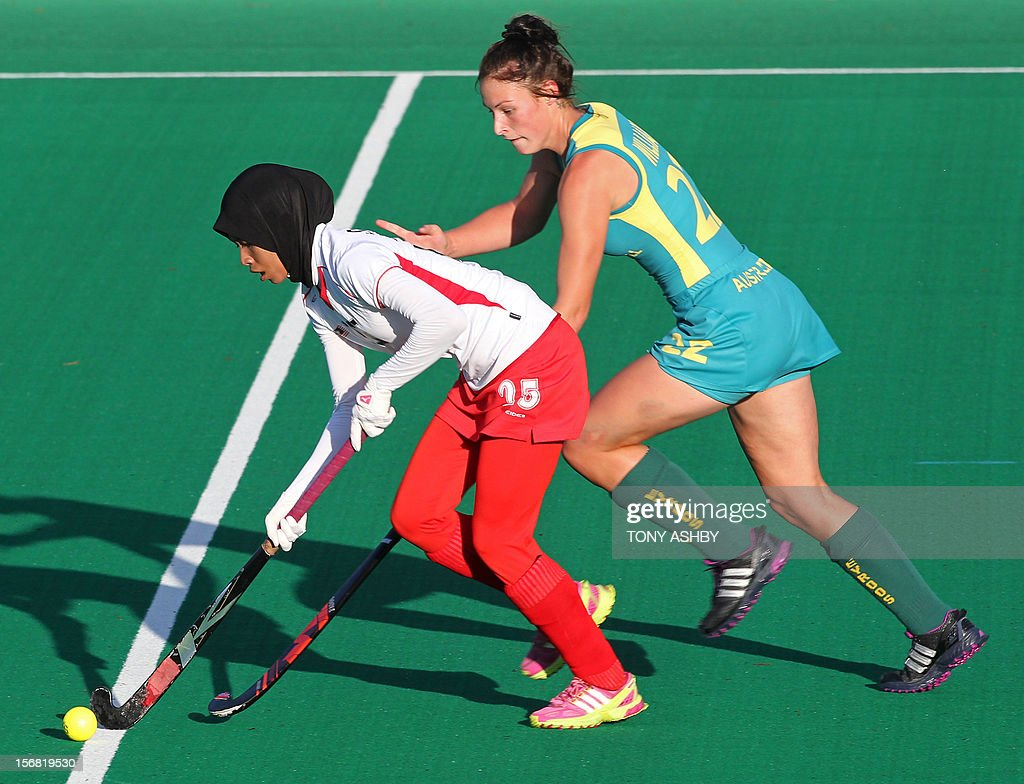 Raja Nor Sharinah Raja Shabudin (L) of Malaysia dribbles the ball in front of Mariah Williams (R) of Australia during their women's Under 21's match at the International Super Series hockey tournament in Perth on November 22, 2012. Australia won 3-2.