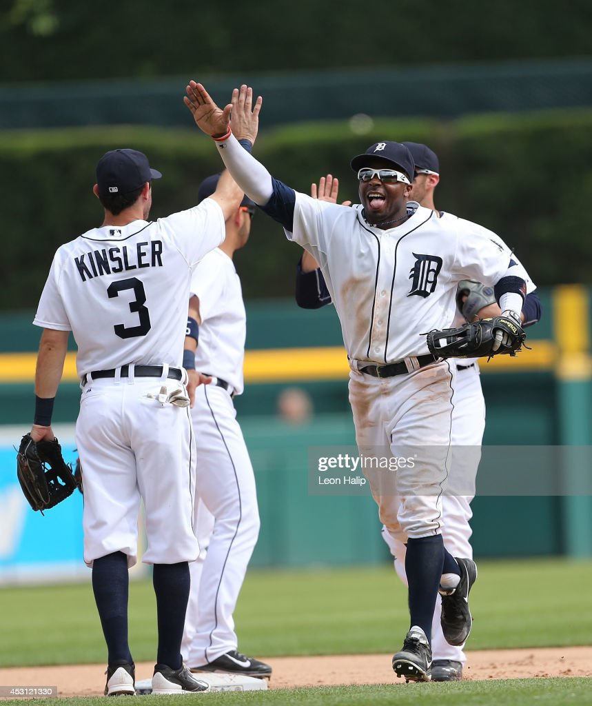 Rajai Davis #20 and Ian Kinsler #3 of the Detroit Tigers celebrate a win over the Colorado Rockies at Comerica Park on August 3, 2014 in Detroit, Michigan. The Tigers defeated the Rockies 4-0.