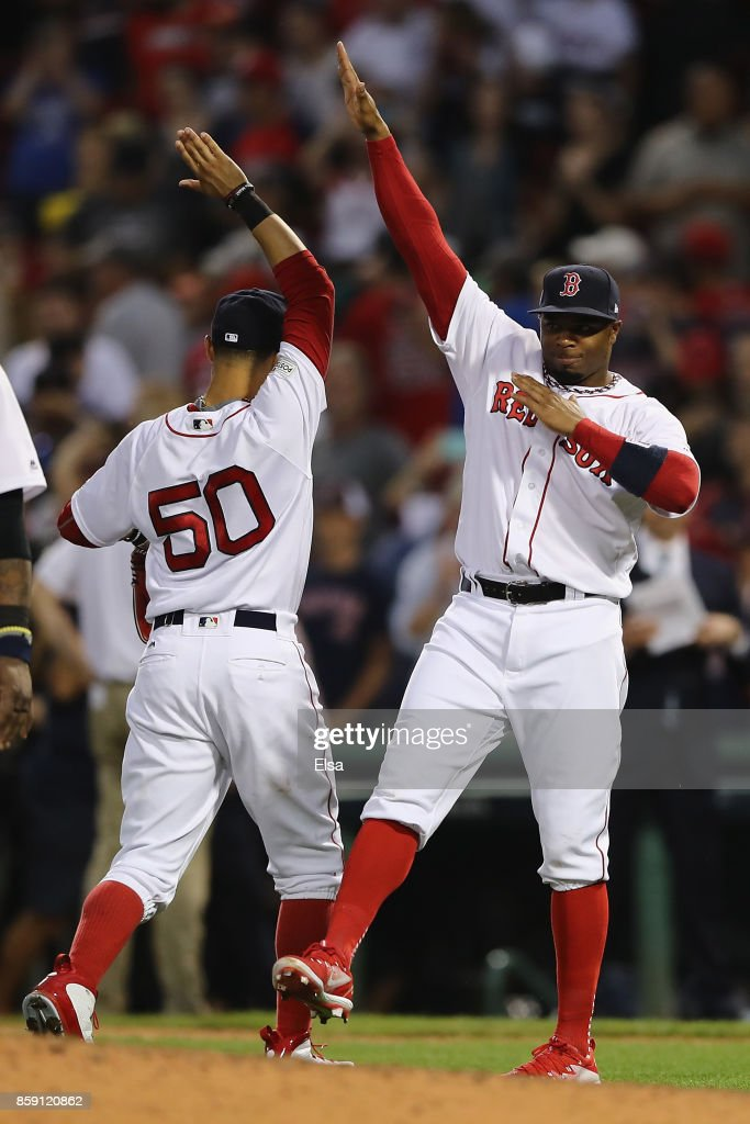 Rajai Davis #25 of the Boston Red Sox (R) celebrates with Mookie Betts #50 after defeating the Houston Astros 10-3 in game three of the American League Division Series at Fenway Park on October 8, 2017 in Boston, Massachusetts.