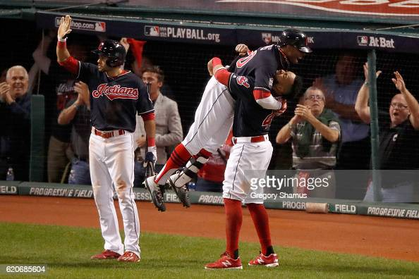 Rajai Davis of the Cleveland Indians celebrates with Carlos Santana after hitting a tworun home run during the eighth inning to tie the game 66...