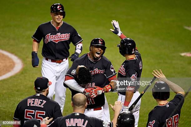Rajai Davis of the Cleveland Indians celebrates with teammates after hitting a tworun home run during the eighth inning to tie the game 66 against...