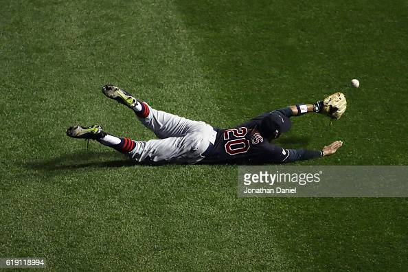 Rajai Davis of the Cleveland Indians dives and fails to make a catch in the first inning against the Chicago Cubs in Game Four of the 2016 World...