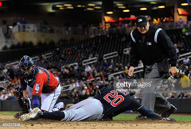 Rajai Davis of the Cleveland Indians slides safely to score a run as Kurt Suzuki of the Minnesota Twins defends home plate during the fifth inning of...