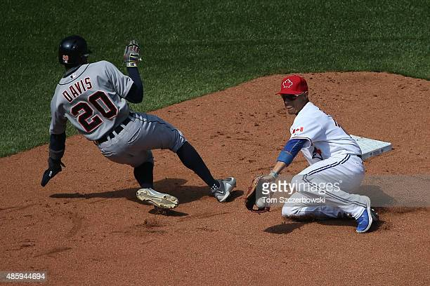 Rajai Davis of the Detroit Tigers gets back to second base safely on a pickoff attempt in the sixth inning during MLB game action as Ryan Goins of...